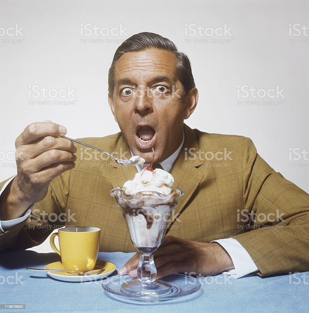 Mature man eating sundae against white background, close-up stock photo