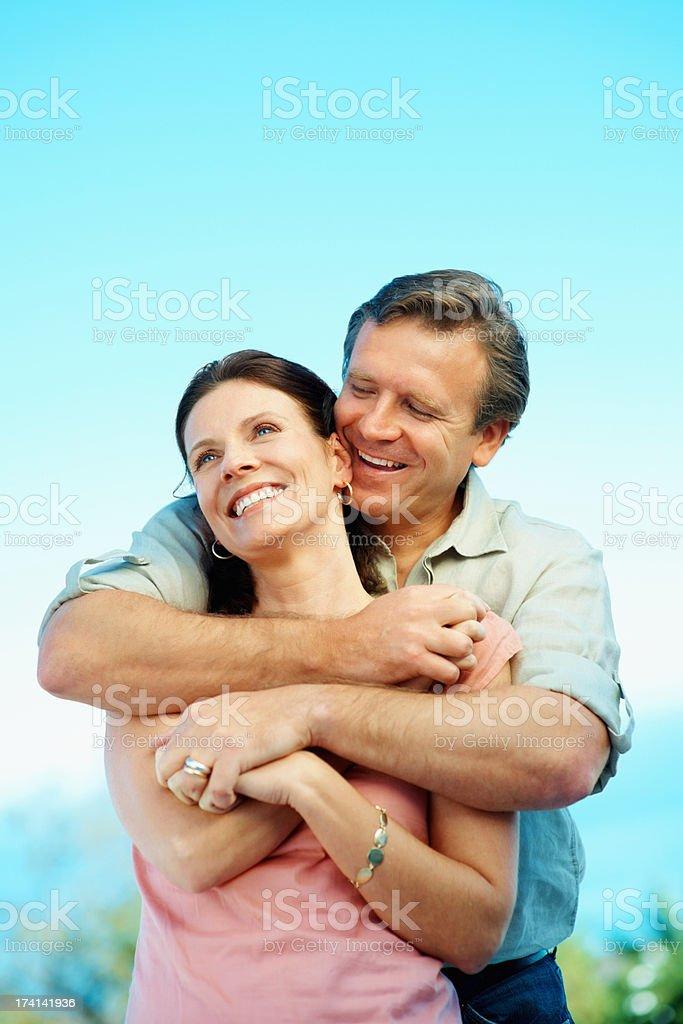 Mature man embracing a cute woman against blue sky stock photo