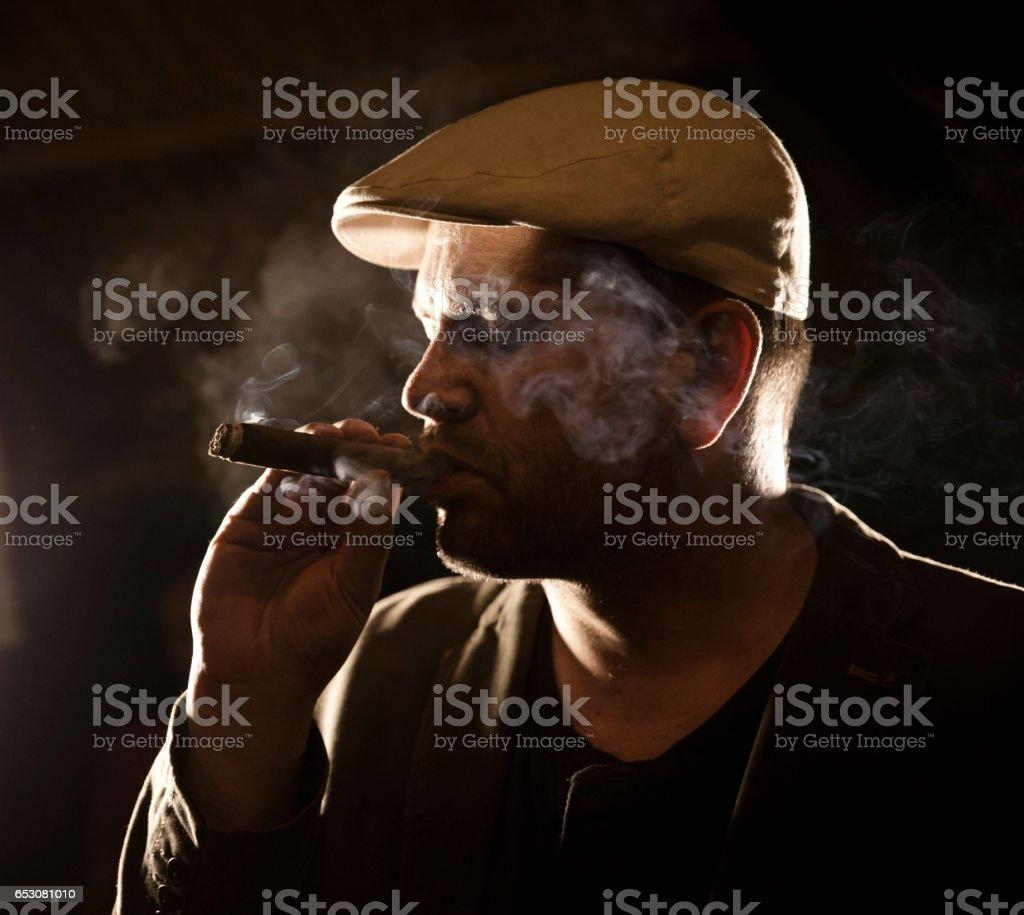 Mature man enjoying a cigar. stock photo