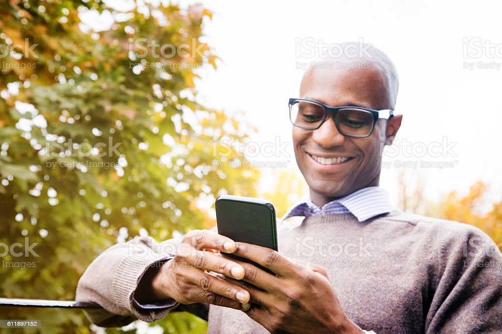 Mature man enjoying social networking on mobile phone stock photo