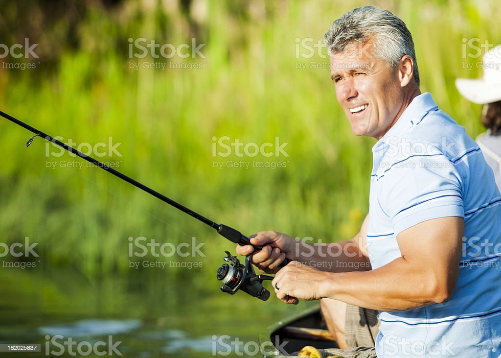 Mature Man Fishing From a Boat stock photo