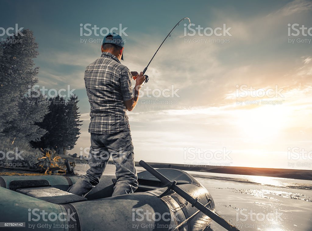 Mature man fishing on the lake stock photo
