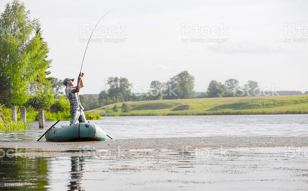 Mature man fishing on the lake stock photo