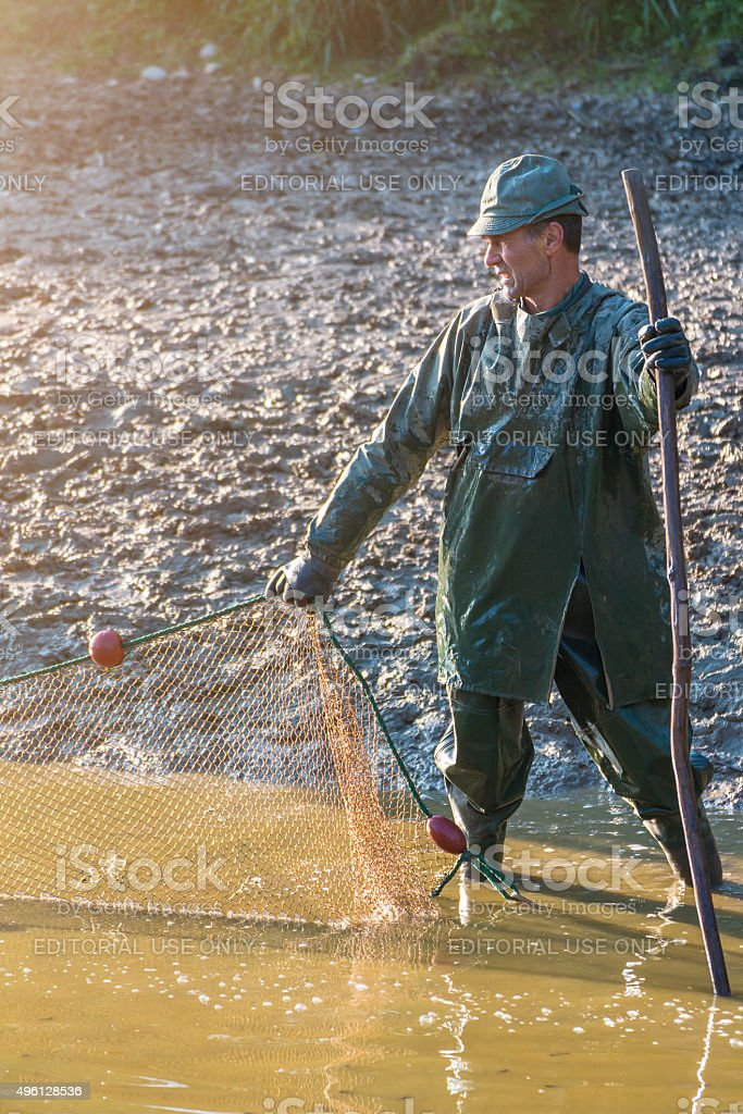 Mature man fishing with large net in french pond stock photo
