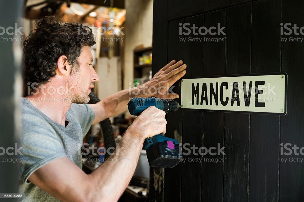 Mature man fixing mancave sign on wooden door stock photo