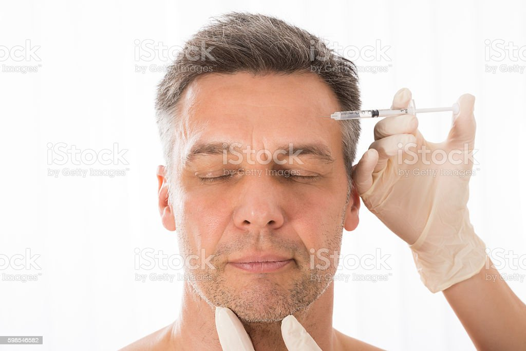 Mature Man Get Injection On His Face stock photo