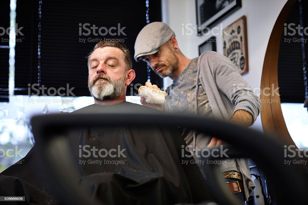 mature man getting a haircut stock photo