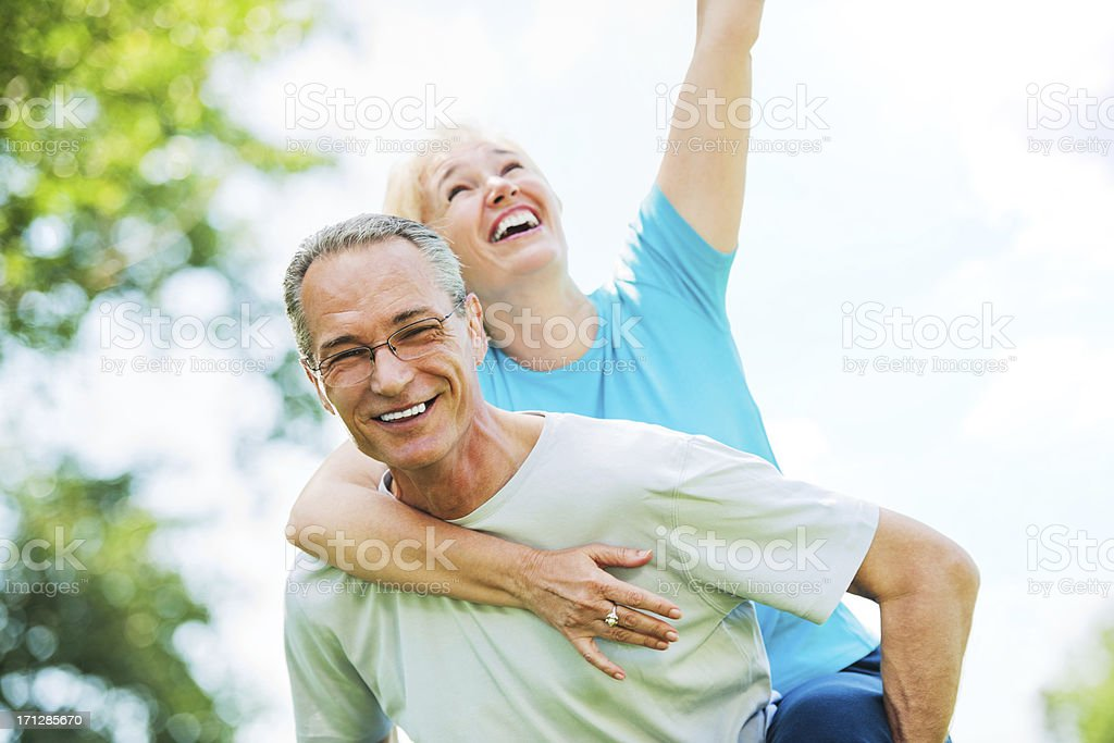 Mature man giving his wife a piggyback ride. royalty-free stock photo