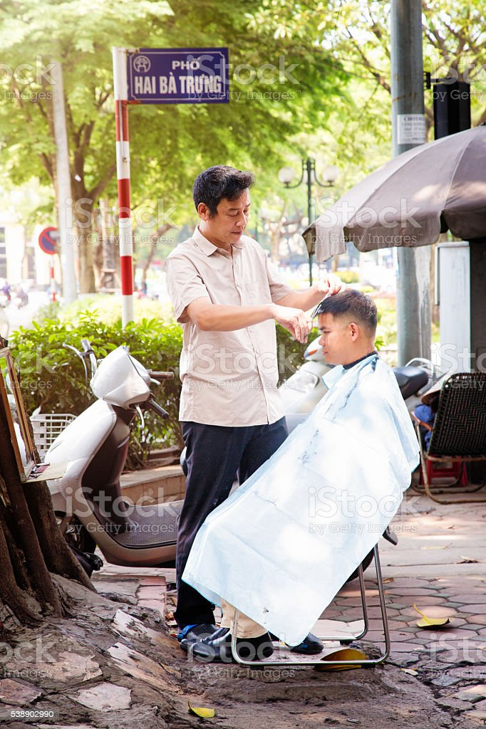 Mature man hairdresser at work in street of Hanoi Vietnam stock photo