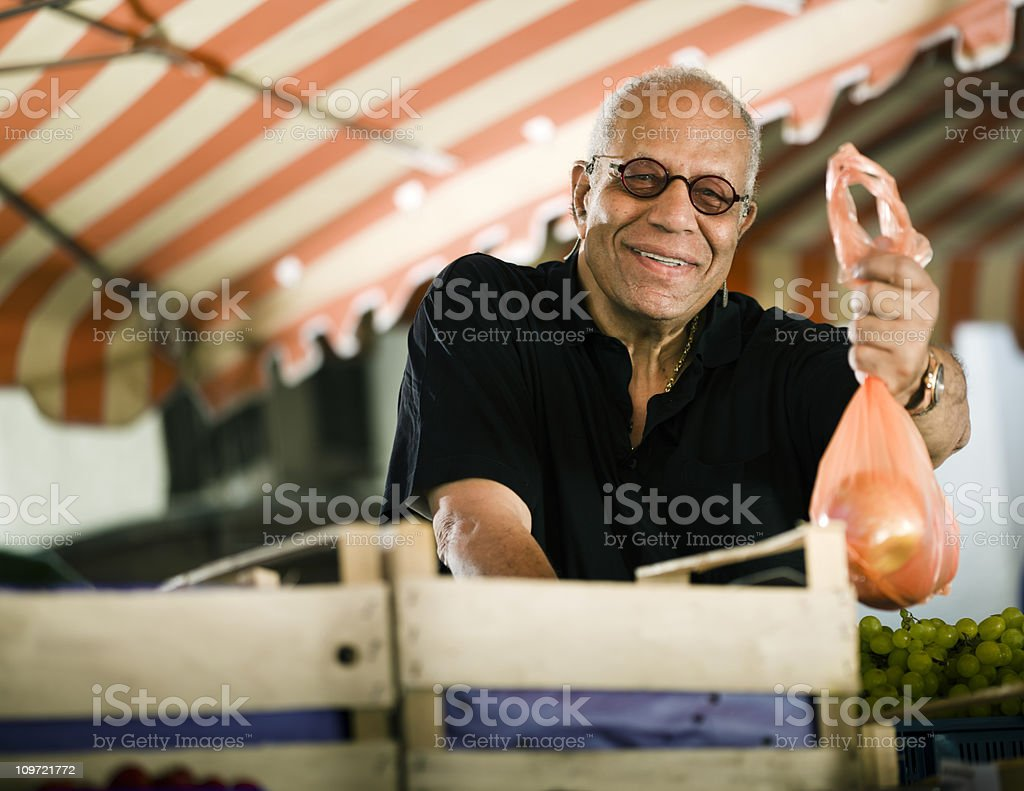Mature Man Handing Out a Bag of Apples royalty-free stock photo