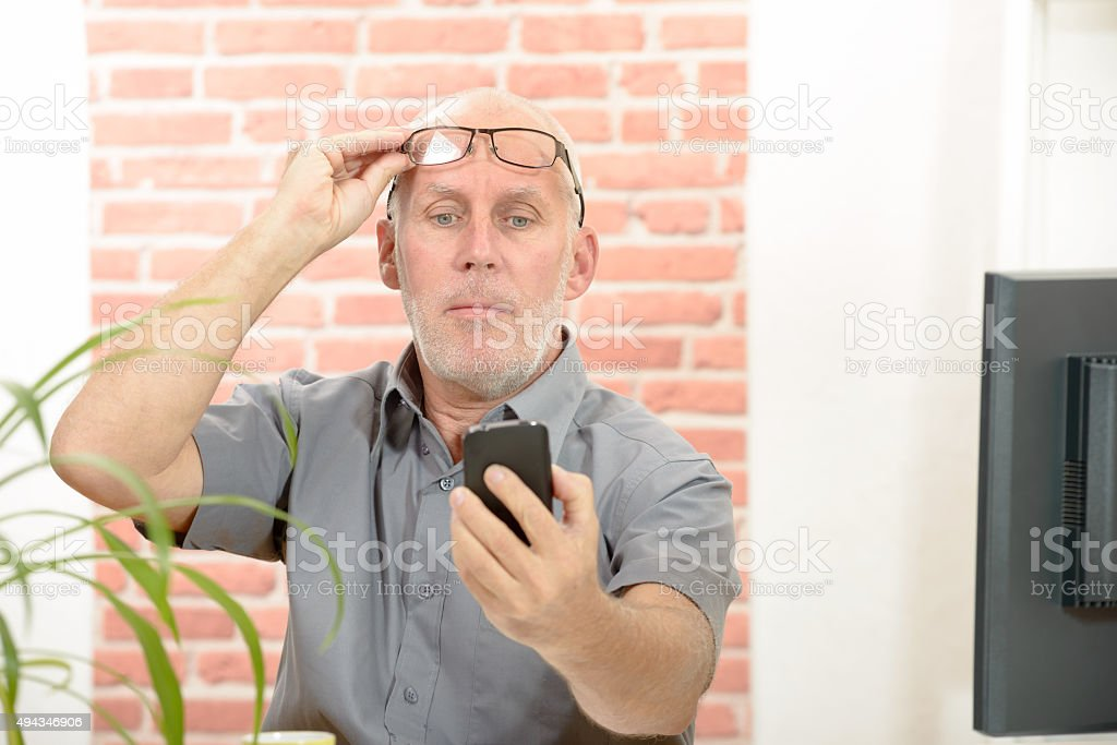 Mature man having trouble seeing phone because of vision problems stock photo