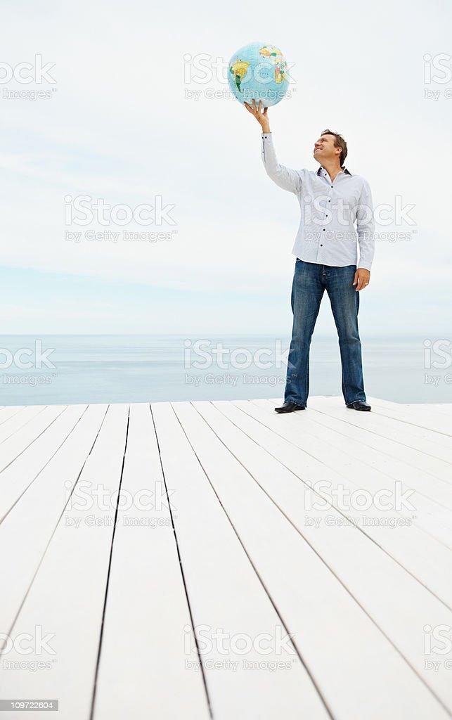 Mature man holding a globe outdoors stock photo