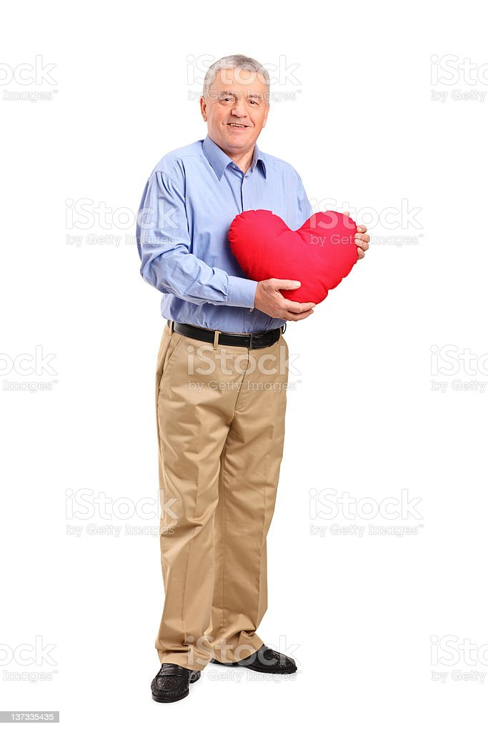Mature man holding a heart shaped pillow royalty-free stock photo