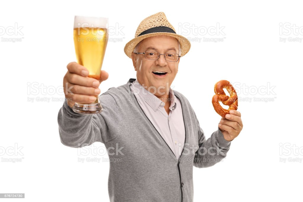 Mature man holding beer and pretzel stock photo