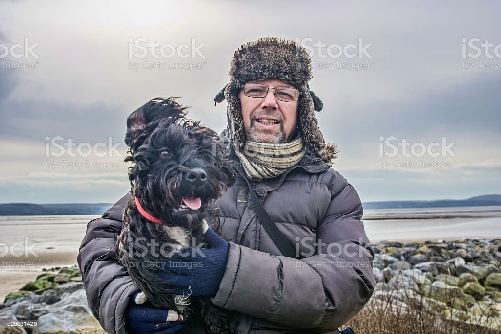 Mature man holding Patterndale Terrier at coast stock photo