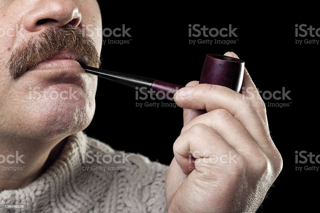 mature man holding smoking pipe in hand isolated on black royalty-free stock photo