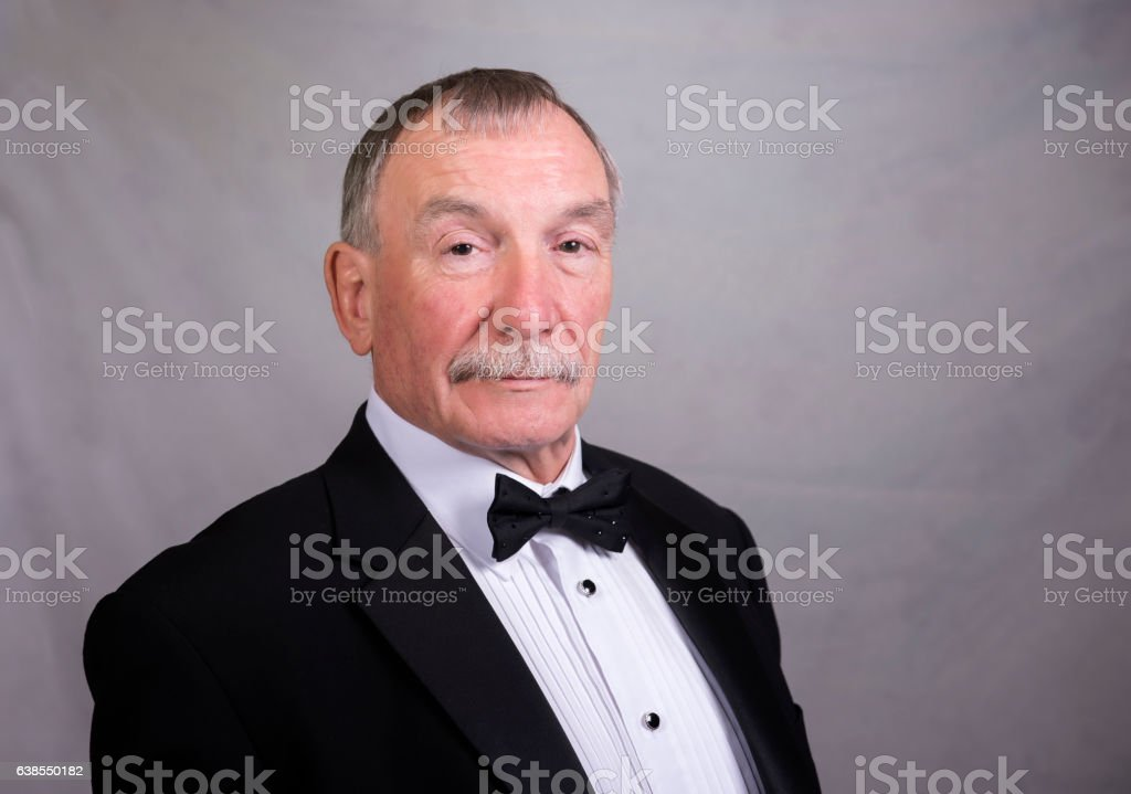 Mature man in a dinner jacket and bow tie. stock photo