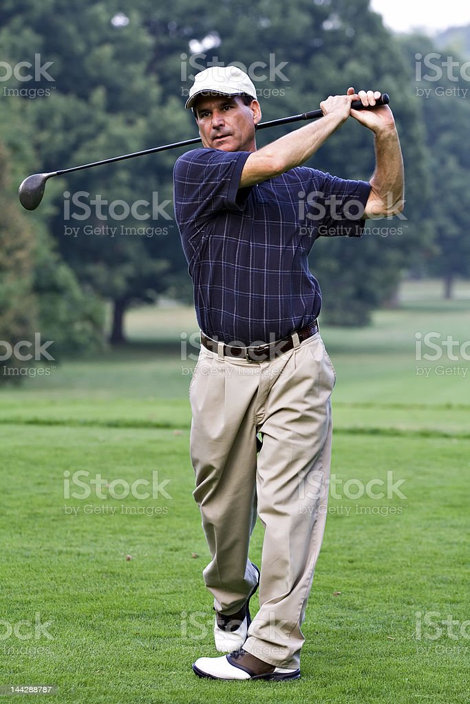 Mature man in a golfing pose after taking a shot royalty-free stock photo