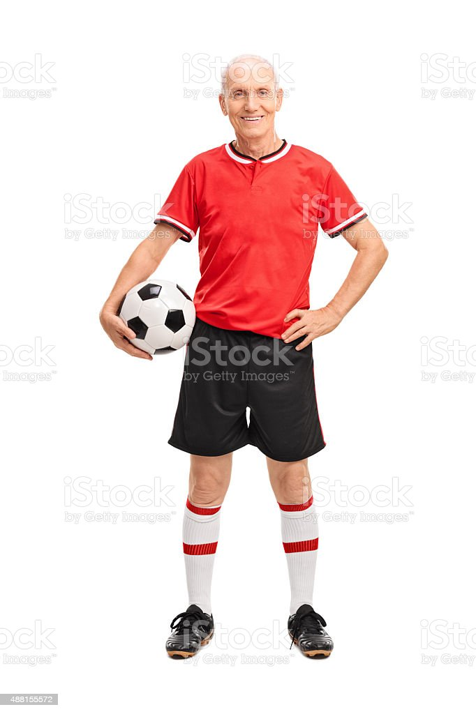 Mature man in a red jersey holding a football stock photo
