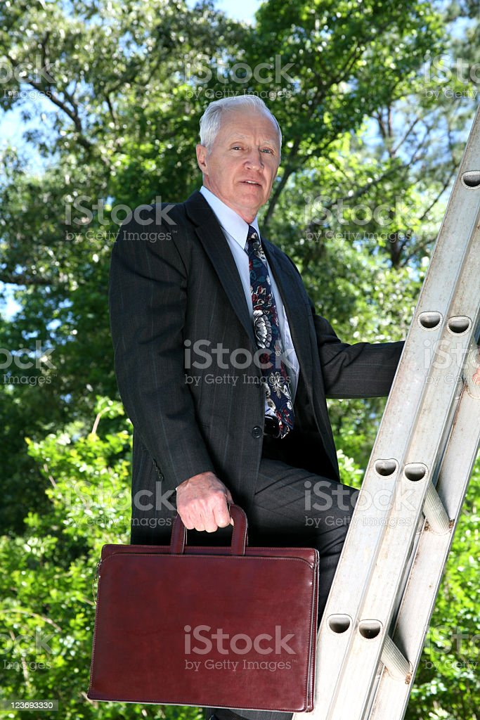 Mature man in business suit climbing ladder royalty-free stock photo