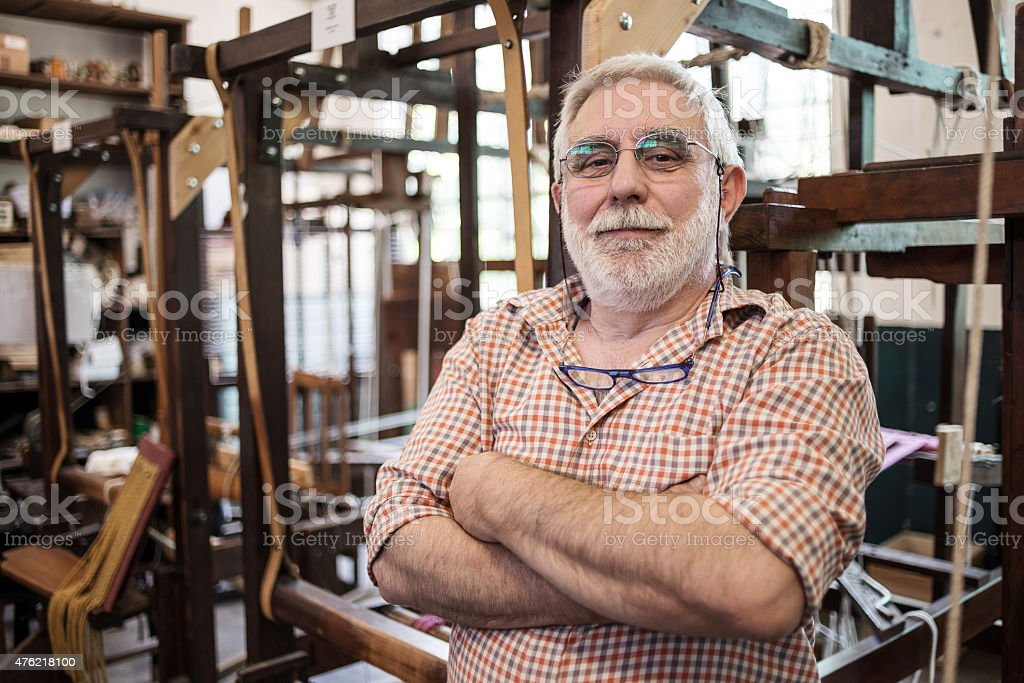 Mature man in his artisanal handicraft traditional textile factory stock photo