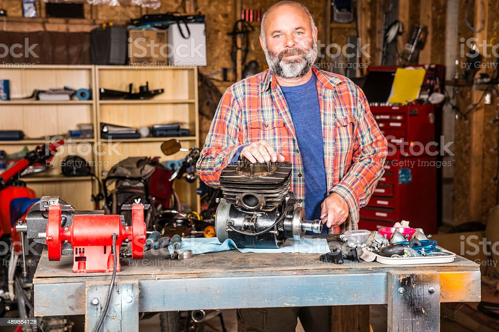 Mature man in his motorcycle workshop stock photo