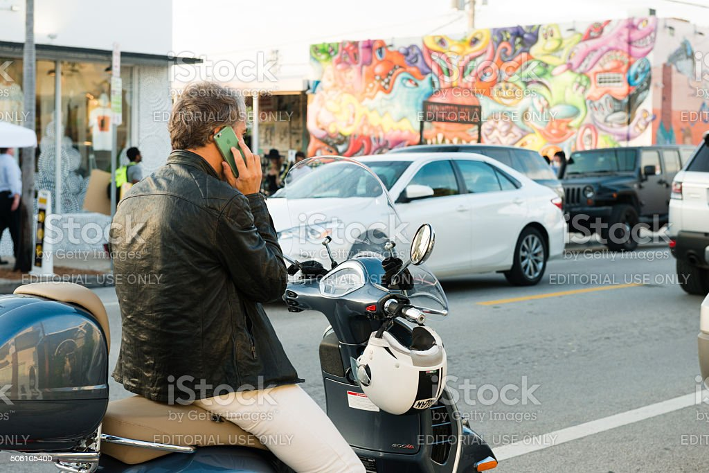 Mature Man in Miami Parked with Moped Talks on Mobile stock photo