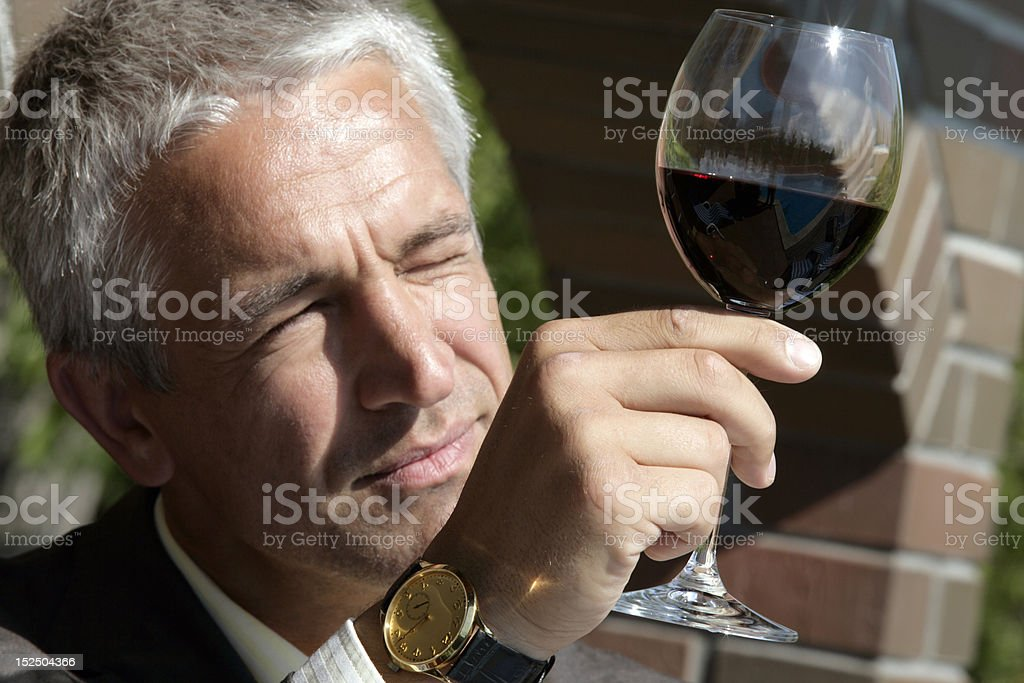 Mature man inspecting a glass of red wine royalty-free stock photo
