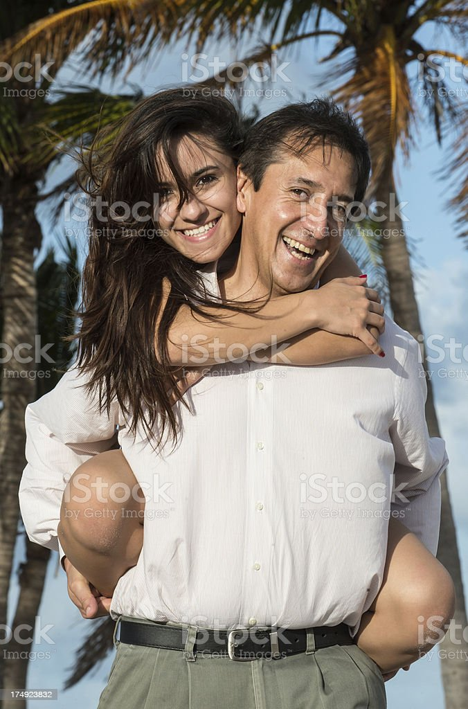 A mature man is having fun carrying a young woman. stock photo