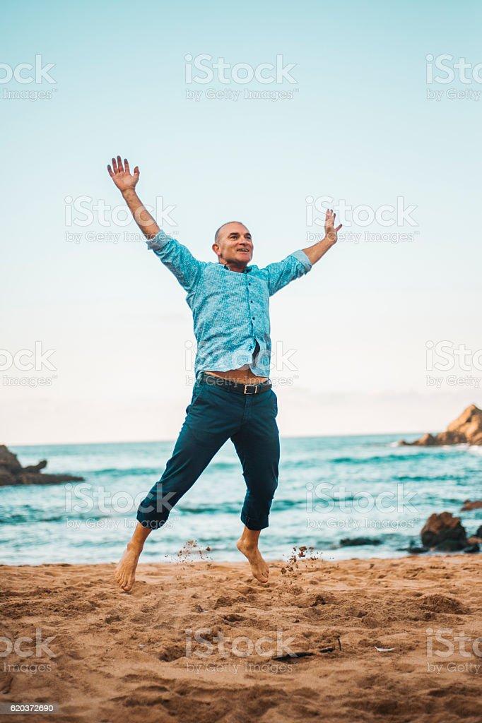 Mature man jumping stock photo