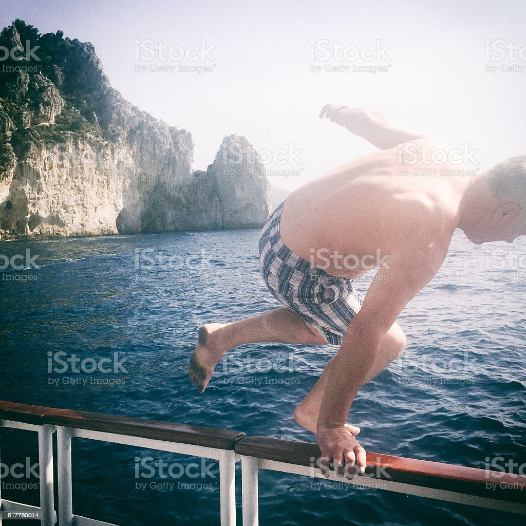 Mature Man Jumps Over Barrier into the Sea stock photo