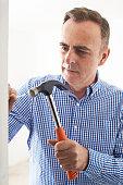 Mature Man Knocking Nail Into Wall With Hammer