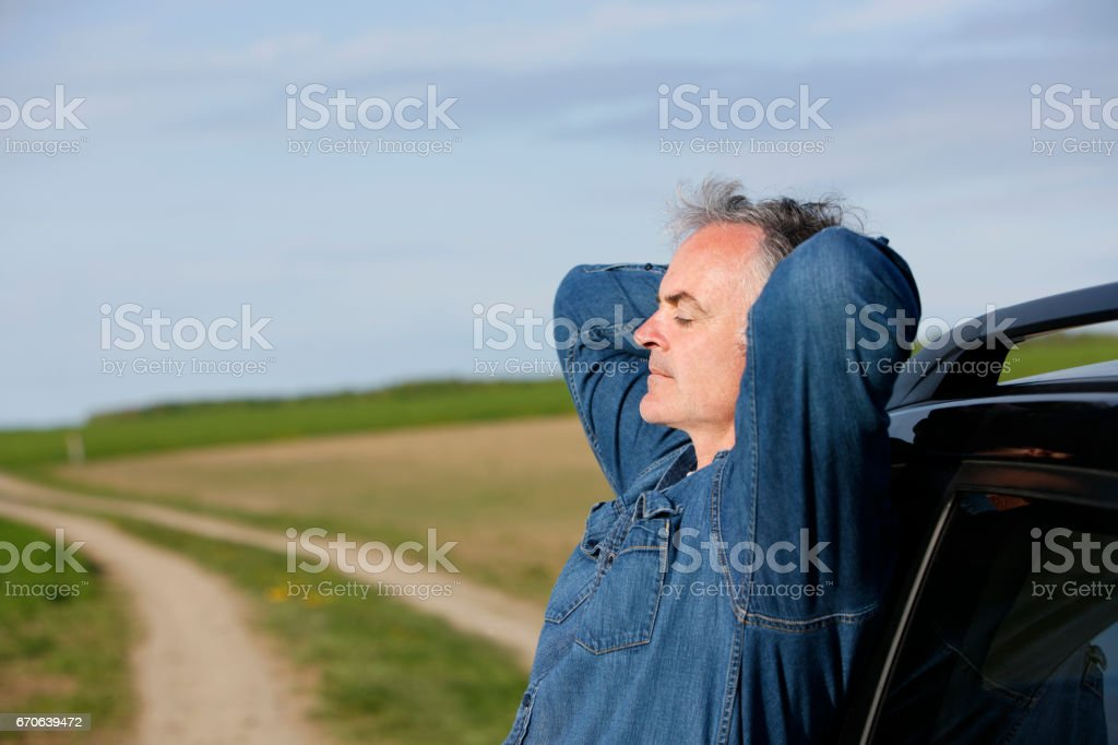 Mature man leaning on automobile. stock photo