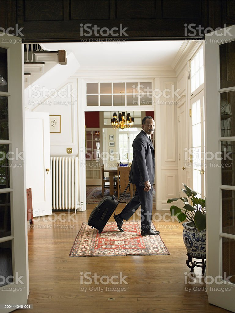 Mature man leaving home with luggage stock photo