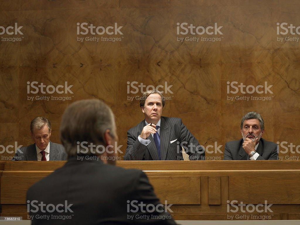 Mature man listening to speaker at podium, rear view royalty-free stock photo