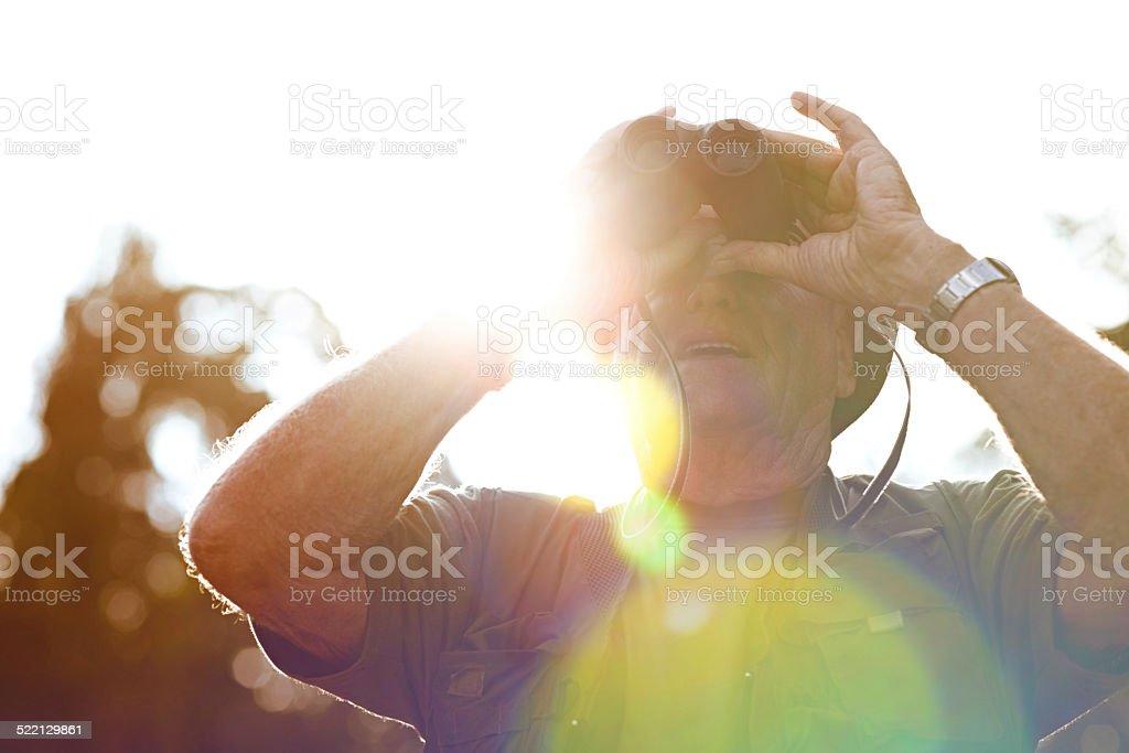 Mature man looking through binoculars stock photo