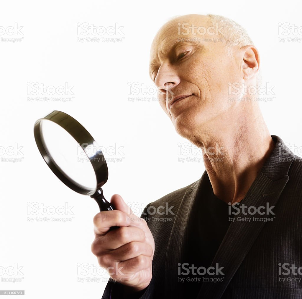 Mature man looking through magnifying glass, interested, with tilted head stock photo