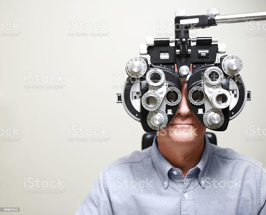 Mature Man looking through Phoroptor stock photo