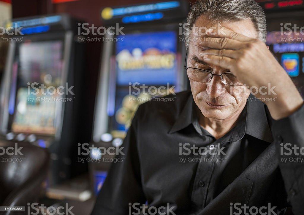 Mature man loosing his money on slot machines. royalty-free stock photo