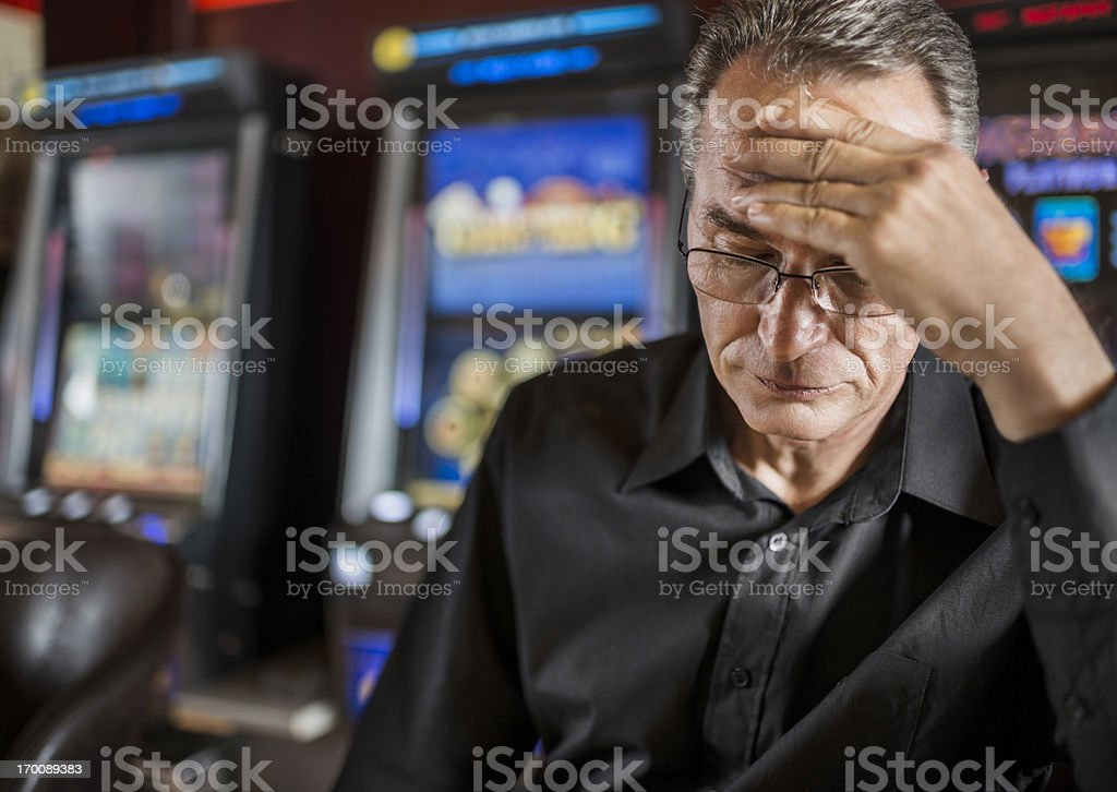 Mature man loosing his money on slot machines. stock photo