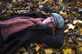 Mature man lying in a pile of leaves outdoors