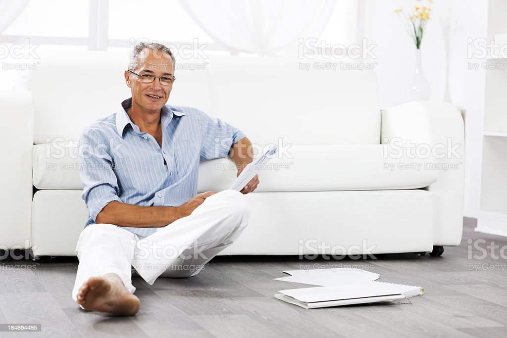 Mature man lying on floor and looking at camera royalty-free stock photo
