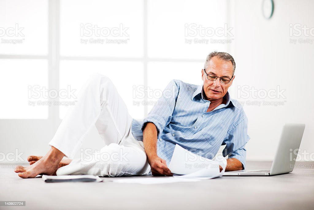 Mature man lying on floor and looking at documents royalty-free stock photo