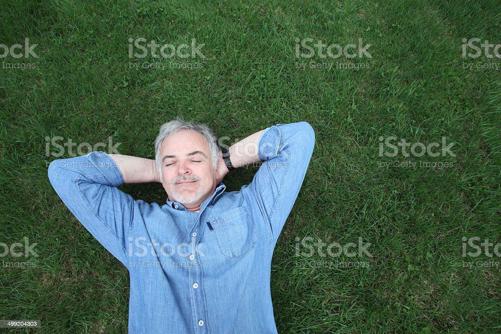 mature man lying on grass. stock photo