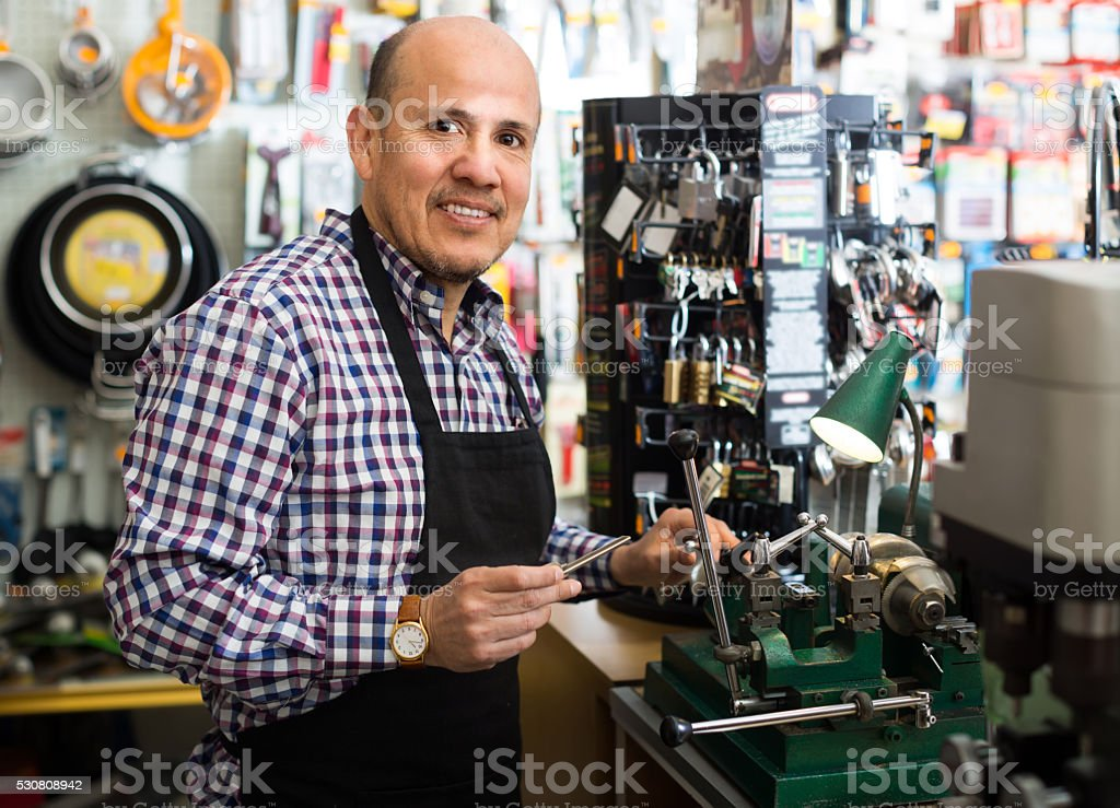 Mature man making duplicates of keys stock photo