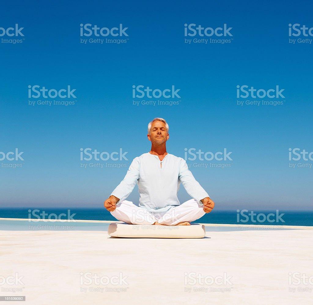 Mature man meditating on beach royalty-free stock photo
