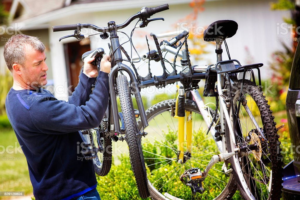 Mature man mounting bicylcles on car rack stock photo