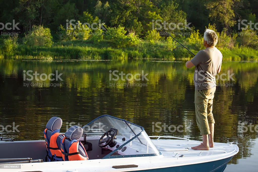 Mature man on a motor boat. Fishing. stock photo