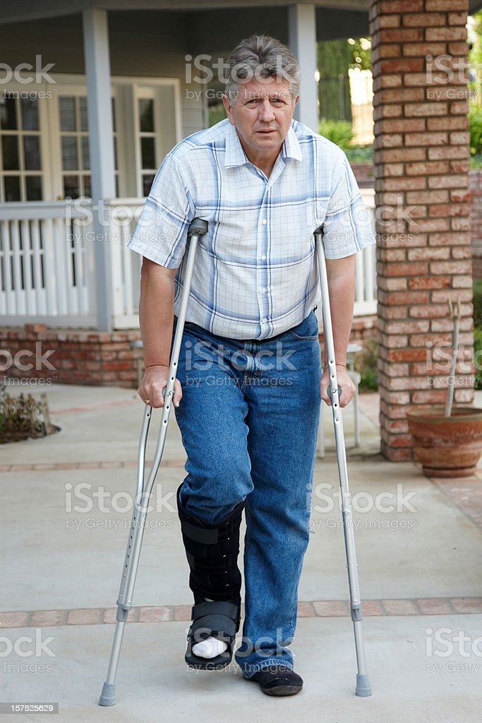 Mature man on crutches royalty-free stock photo