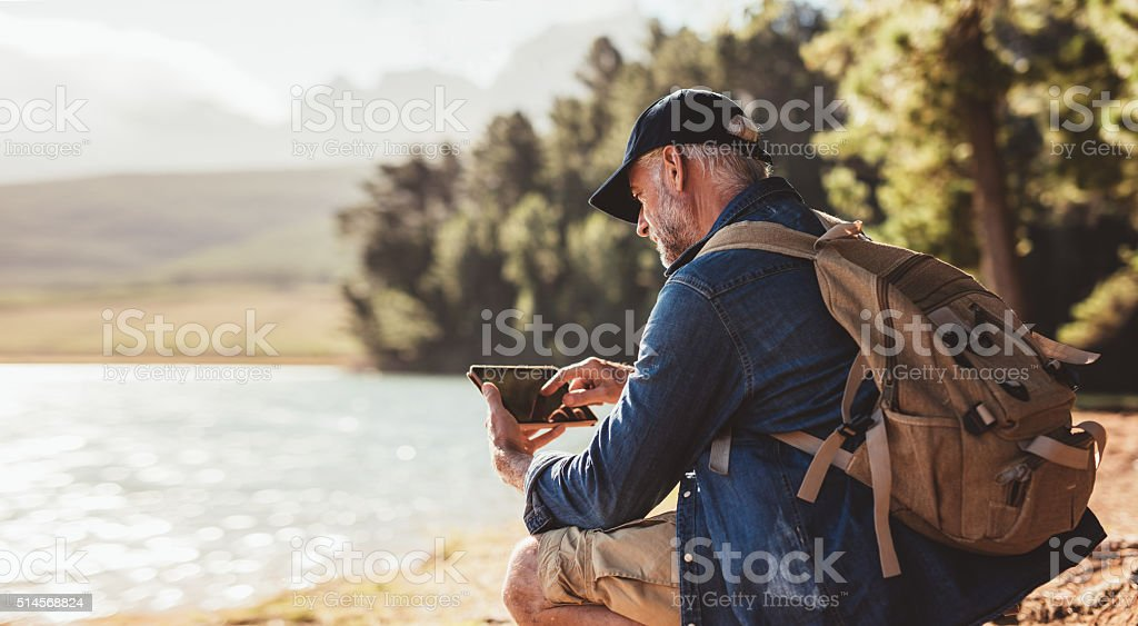 Mature man on hike in nature using digital tablet stock photo